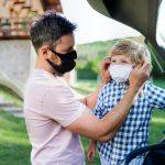 man putting mask on child