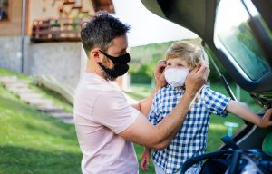 man putting mask on child